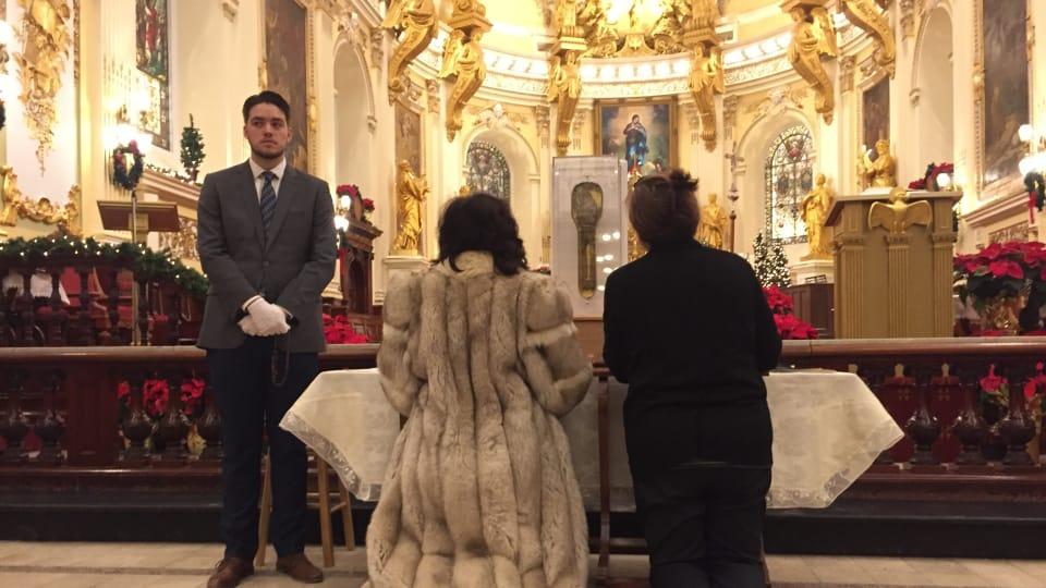 Deux personnes se recueillent devant la relique de saint François Xavier. Photo : Radio-Canada/Cimon Leblanc